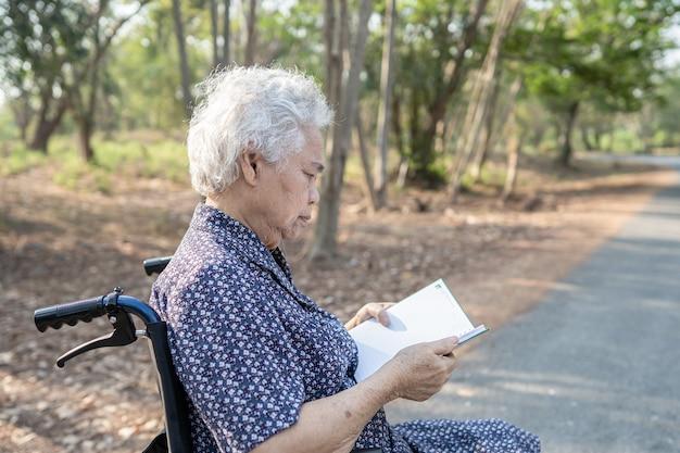 Paciente de mulher idosa asiática sênior ou idosa lendo um livro enquanto está sentado na cama na enfermaria do hospital de enfermagem, conceito médico forte saudável.
