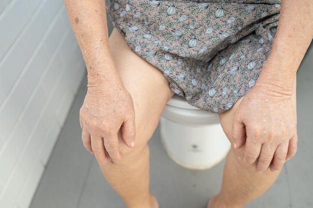 Paciente de mulher idosa asiática sênior ou idosa sentado no autoclismo no banheiro.