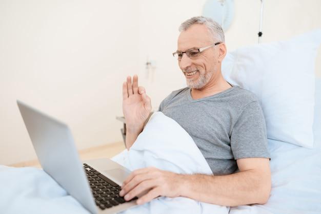 Paciente de reabilitação colagem usa laptop na cama