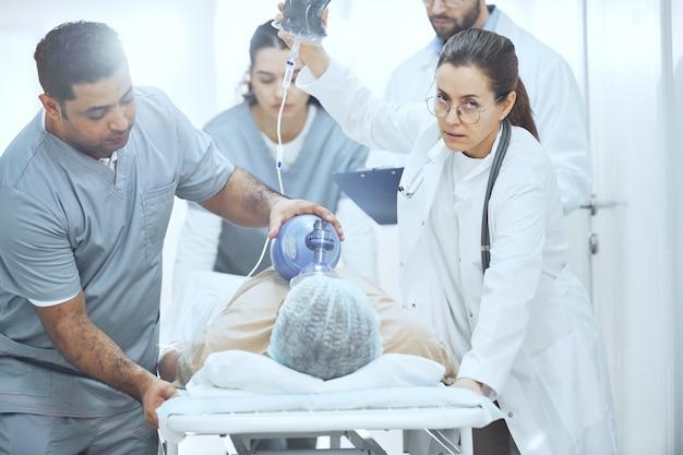 Paciente deitado com máscara de oxigênio enquanto os médicos realizam uma reanimação com desfibrilador no hospital