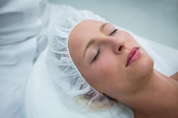 Paciente deitado na cama enquanto recebe tratamento cosmético