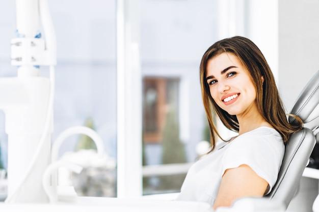 Paciente dental consideravelmente feliz e sorrindo que senta-se na cadeira dental no escritório dental.