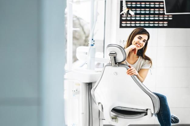Paciente dental muito feliz e sorridente, sentado na cadeira odontológica no consultório odontológico.