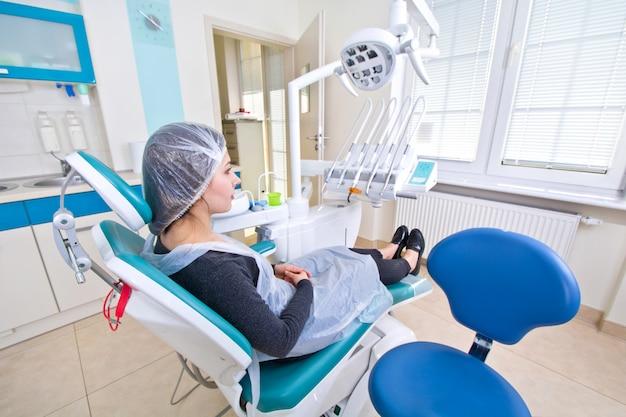 Paciente do sexo feminino à espera de tratamento dentário em uma cadeira odontológica.