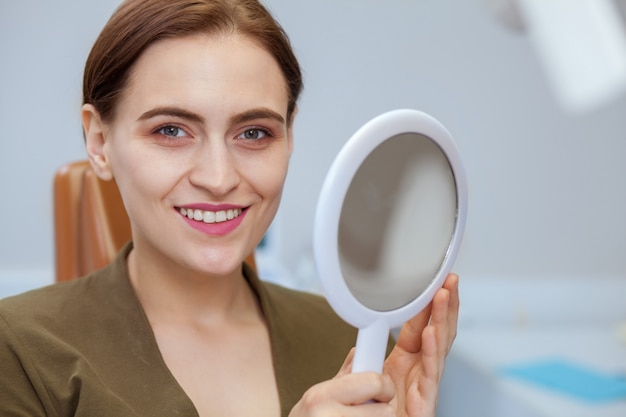 Paciente do sexo feminino alegre na clínica odontológica, copie o espaço
