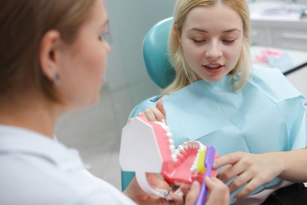 Paciente do sexo feminino aprendendo a escovar os dentes corretamente com seu dentista