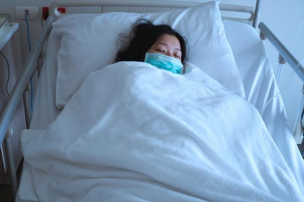 Paciente do sexo feminino asiático dormindo na cama do hospital para recuperar a doença