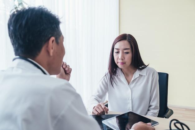 Paciente do sexo feminino asiático e médico estão discutindo
