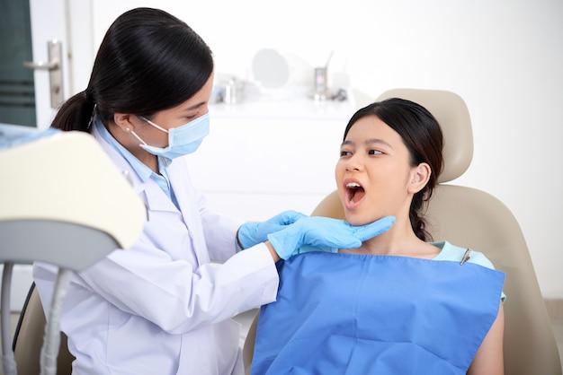 Paciente do sexo feminino asiático sentado na cadeira com a boca aberta e dentista olhando para os dentes