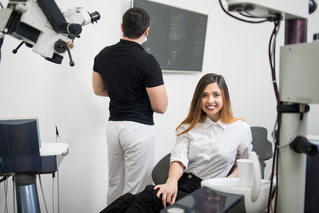 Paciente do sexo feminino bonito sentado na cadeira odontológica, sorrindo após o tratamento na clínica odontológica moderna.