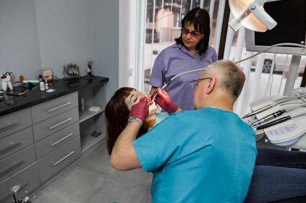 Paciente do sexo feminino com a boca aberta durante o tratamento de perfuração no dentista. equipe odontológica profissional homem e mulher fazendo tratamento para paciente jovem