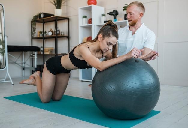 Paciente do sexo feminino com fisioterapeuta fazendo exercícios com bola
