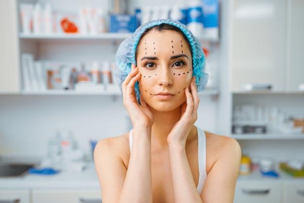 Paciente do sexo feminino com marcadores no rosto, consultório da esteticista. procedimento de rejuvenescimento em salão de esteticista. cirurgia estética contra rugas, preparação para o botox