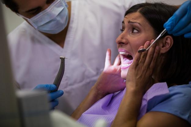 Paciente do sexo feminino com medo durante um check-up dental