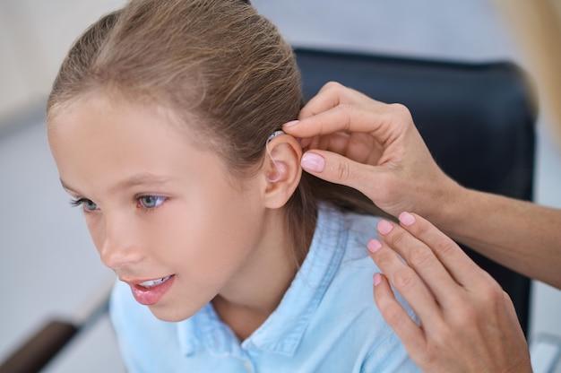 Paciente do sexo feminino com um aparelho auditivo conectado atrás da orelha