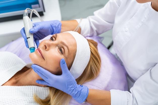 Paciente do sexo feminino com uma bandana deitada em um sofá durante um procedimento cosmético de cuidados com a pele