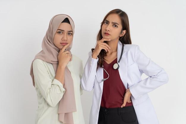 Paciente do sexo feminino com véu e bela médica de uniforme branco, segurando o queixo com expressão pensando em ...