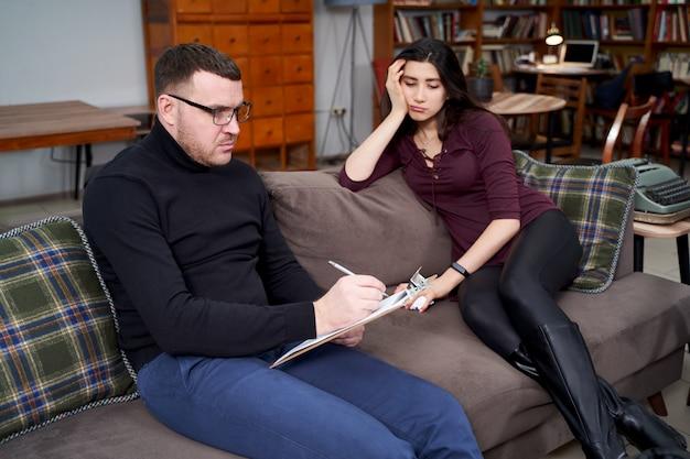 Paciente do sexo feminino conversando com seu terapeuta, que está fazendo anotações no escritório particular em casa