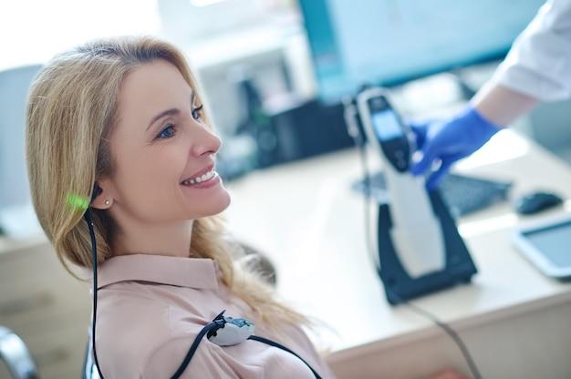 Paciente do sexo feminino de meia-idade sendo testada para acuidade auditiva