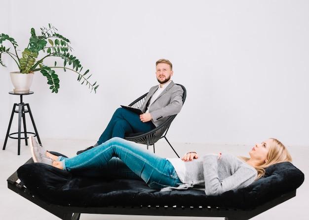 Paciente do sexo feminino deitado no sofá na frente de seu psicólogo contemplado na clínica