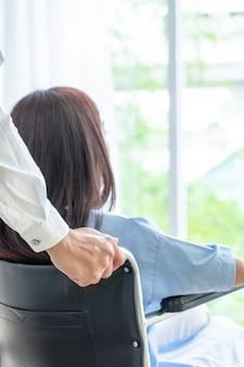 Paciente do sexo feminino em cadeira de rodas com médico sênior