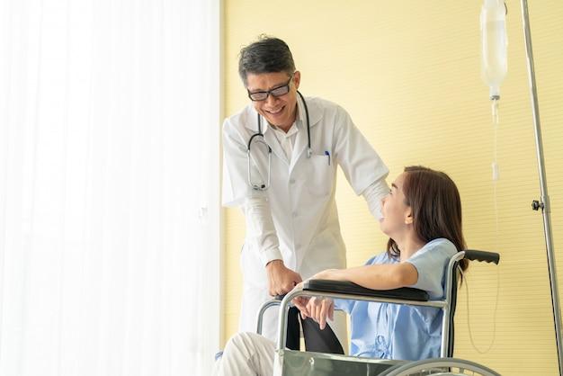 Paciente do sexo feminino em cadeira de rodas com médico