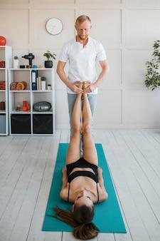 Paciente do sexo feminino em fisioterapia com fisioterapeuta masculino