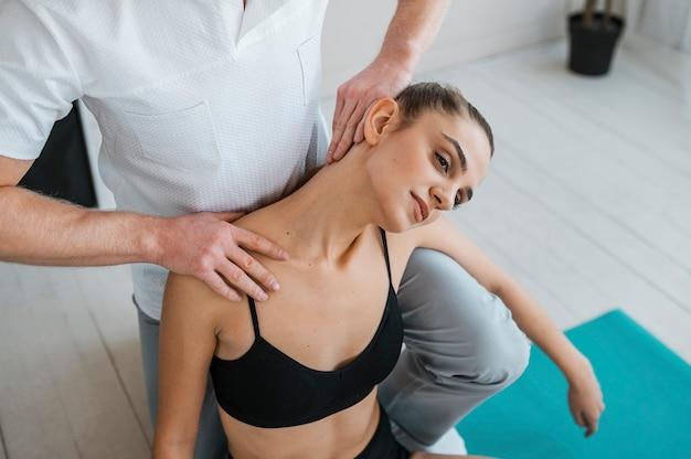 Paciente do sexo feminino em fisioterapia fazendo exercícios com fisioterapeuta
