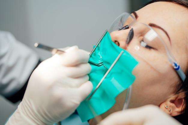 Paciente do sexo feminino em óculos de proteção com os olhos fechados, tendo tratamento no consultório odontológico.