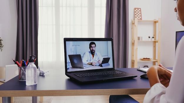 Paciente do sexo feminino em uma videochamada com um médico falando sobre sua doença
