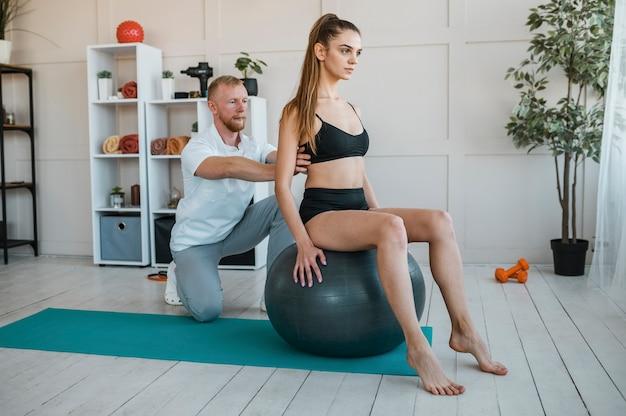 Paciente do sexo feminino fazendo exercícios com bola e fisioterapeuta