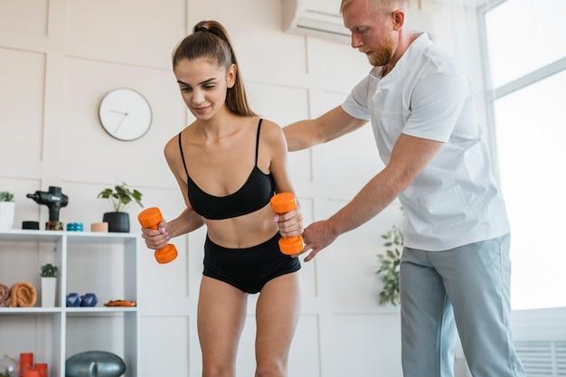 Paciente do sexo feminino fazendo exercícios com halteres e fisioterapeuta masculino