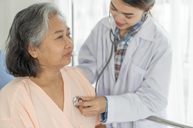 Paciente do sexo feminino idoso idoso médico examinar no paciente do hospital - conceito sênior de medicina e saúde