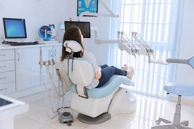Paciente do sexo feminino jovem sentado na cadeira na clínica odontológica