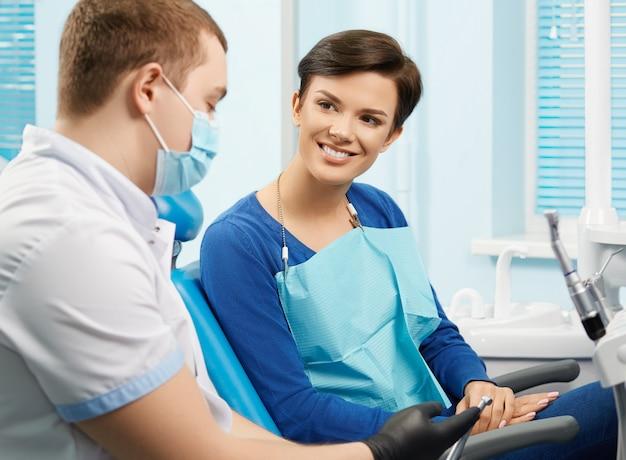 Paciente do sexo feminino jovem visitar consultório dentista. bela mulher sentada na cadeira odontológica. dentista, mostrando o equipamento dental. clinica odontológica. estomatologia