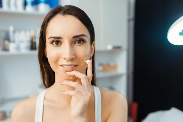 Paciente do sexo feminino mostra creme no dedo no escritório da esteticista. procedimento de rejuvenescimento em salão de esteticista.