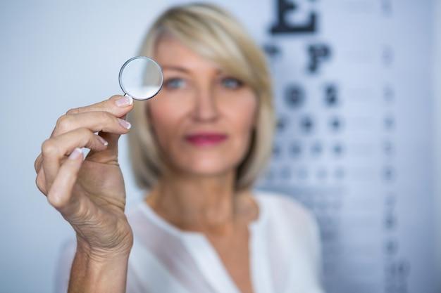 Paciente do sexo feminino olhando através de lupa