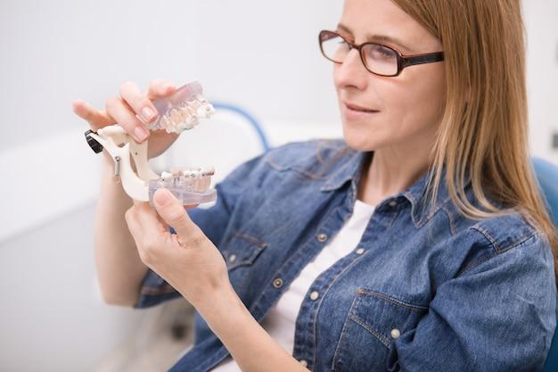 Paciente do sexo feminino olhando para um modelo dentário com aparelho ortodôntico na clínica odontológica