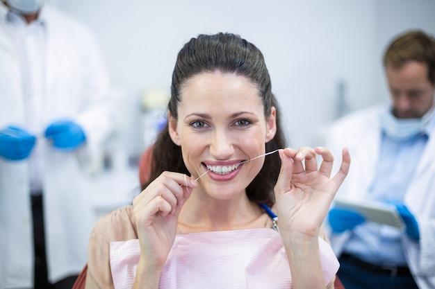 Paciente do sexo feminino passando fio dental