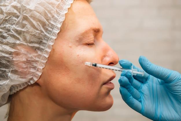 Paciente do sexo feminino recebendo injeção de ácido hialurônico