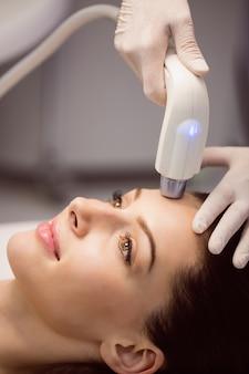 Paciente do sexo feminino recebendo tratamento cosmético