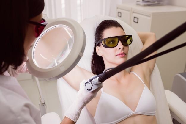 Paciente do sexo feminino recebendo tratamento de depilação a laser