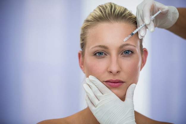 Paciente do sexo feminino recebendo uma injeção de botox na testa