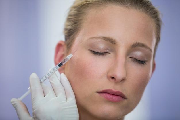 Paciente do sexo feminino recebendo uma injeção de botox no rosto