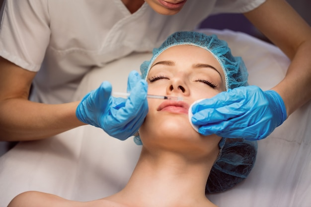 Paciente do sexo feminino recebendo uma injeção no rosto