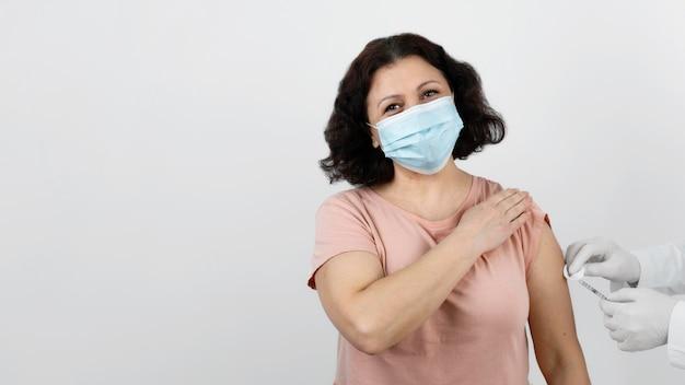 Paciente do sexo feminino recebendo vacina com espaço de cópia