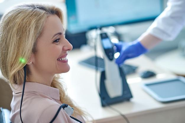 Paciente do sexo feminino satisfeita sorrindo durante o teste de audiometria