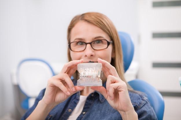 Paciente do sexo feminino segurando modelo dentário com aparelho, aguardando exame médico no dentista