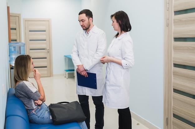 Paciente do sexo feminino sendo tranquilizado por médicos no quarto de hospital