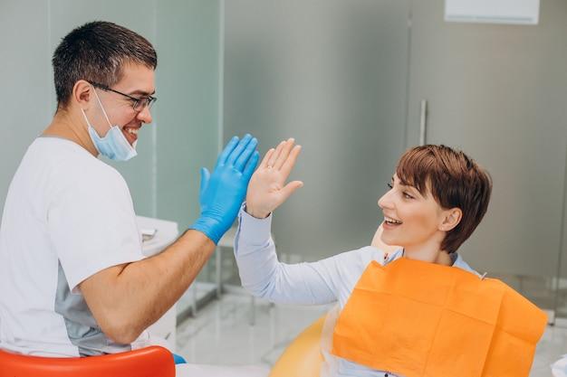 Paciente do sexo feminino sentada em uma cadeira de dentista fazendo higiene profissional